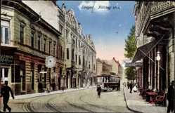 Postcard Segedin Szeged Ungarn, Kölcsey utca, Straßenpartie, Straßenbahn, Geschäfte