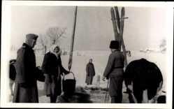 Foto Ak Olchewice? bei Lublin Polen, Wehrmachtsoldaten, Polin am Brunnen, Winter