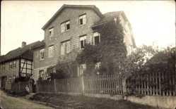 Foto Ak Grünenplan Delligsen, Partie an einem Wohnhaus, Bewohner am Zaun