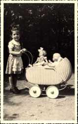 Foto Ak Kleines Mädchen mit ihrem Puppenwagen, Puppen