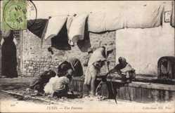 Ak Tunis Tunesien, Une Fontaine, Tunesier am Brunnen, Trocknende Wäsche